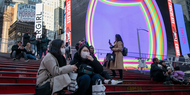 Japanese tourists wear face masks as they sit and chat in Times Square in New York, on Sunday, March 15, 2020. President Donald Trump on Sunday called on Americans to cease hoarding groceries and other supplies, while one of the nation's most senior public health officials called on the nation to act with more urgency to safeguard their health as the coronavirus outbreak continued to spread across the United States. (AP Photo/Wong Maye-E)