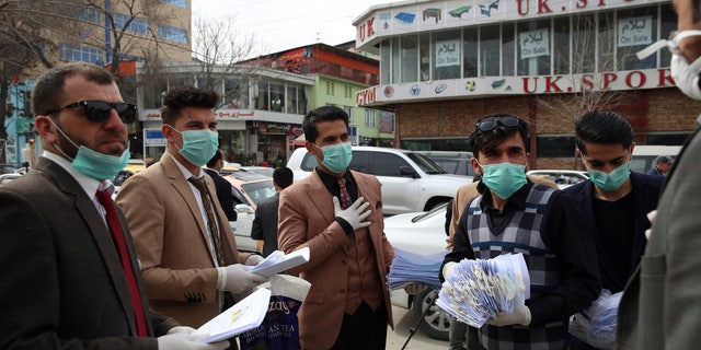 Civil society activists wearing face masks distribute written information to passers-by during a campaign to raise awareness of the new coronavirus in Kabul, Afghanistan, Monday, March 16, 2020. For most people, the new coronavirus causes only mild or moderate symptoms. For some it can cause more severe illness. (AP Photo/Rahmat Gul)
