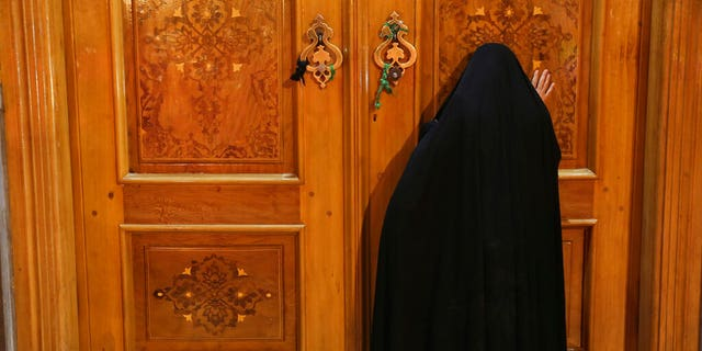 A woman prays behind a closed door of Masoume shrine in the city of Qom, some 80 miles south of the capital Tehran, Iran, Monday, March 16, 2020.