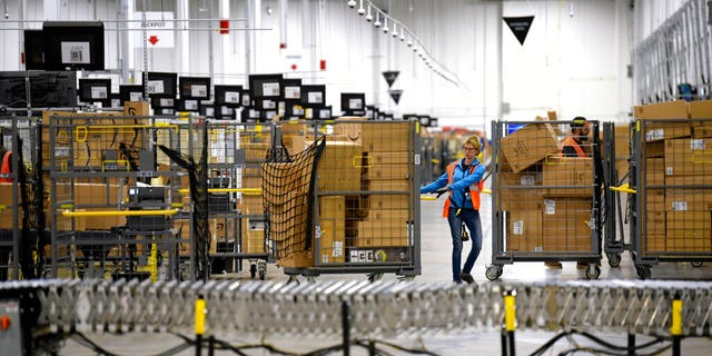 FILE: Associates move bins filled with products at the loading dock of Amazon's then-new fulfillment center in Livonia, Mich.