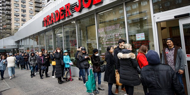Customers wait on line outside a supermarket, Monday, March 16, 2020, in New York. (AP Photo/John Minchillo)