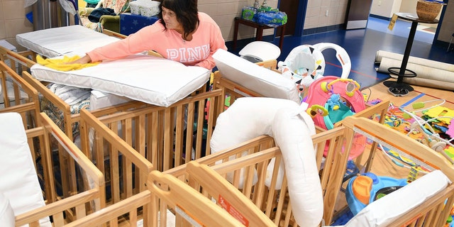 Stacie Burgess cleaning mattresses in the baby beds at The Place for Kids Daycare Center in Beckley. Staff members are cleaning and disinfecting everything in all the Daycare Center rooms and will stay closed until further notice because of the coronavirus. (Rick Barbero/The Register-Herald)