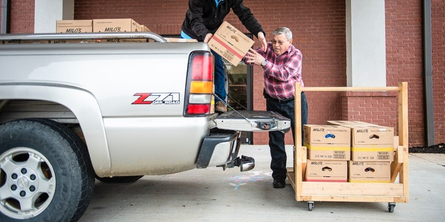 Josh Howard, left, and Ken Runager load boxes of food to be sent to Chestnut Grove Elementary at The Church at Stone River on Monday, March 16, 2020, in Decatur, Ala. Several area schools will be providing food services to students starting Wednesday after students transition to virtual support. (Dan Busey/The Decatur Daily via AP)