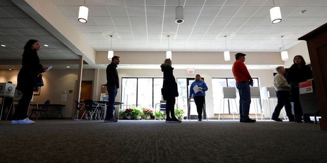 Evanston residents line up for voting at Trinity Lutheran Church in Evanston, Ill., Tuesday, March 17, 2020. Some polling places in Evanston have been moved in an effort to reduce exposure of senior citizens to the COVID-19 coronavirus.(AP Photo/Nam Y. Huh)
