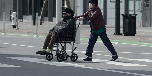 A woman wearing a mask pushes a person in a wheelchair across a street in San Francisco. (AP Photo/Jeff Chiu)