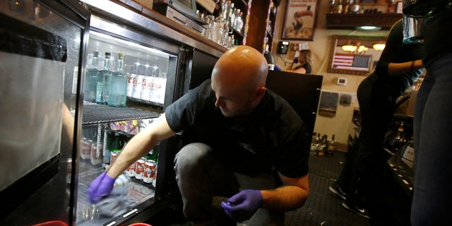 Ryans Sees cleans a beverage cooler as he and other employees prepare to close de Vere's Irish Pub in Sacramento, Calif., Tuesday, March 17, 2020. (AP Photo/Rich Pedroncelli)
