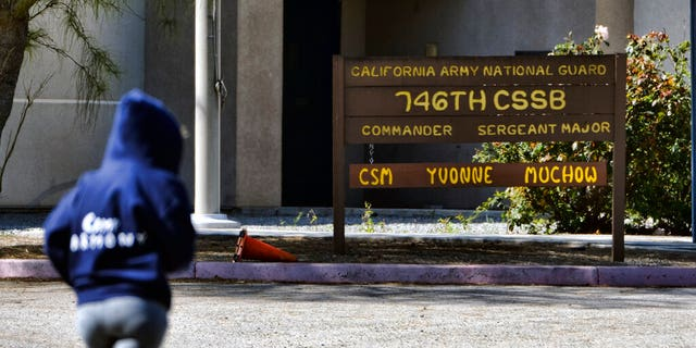 A lone jogger runs past the 746th National Guard unit in Los Angeles, Calif. on Wednesday, March 18, 2020.