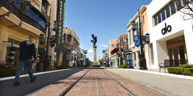 A visitor to the shopping and entertainment complex The Grove walks down a deserted street Wednesday, March 18, 2020, in Los Angeles.