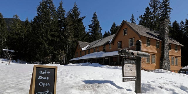 A sign at the National Park Inn at Longmire offers food orders to-go from the inn's restaurant at Mount Rainier National Park, Wednesday, March 18, 2020, in Washington state. Most national parks are remaining open during the outbreak of the new coronavirus, but many are closing visitor centers, shuttles, lodges and restaurants in hopes of containing its spread. (AP Photo/Ted S. Warren)