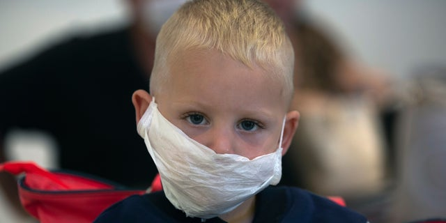 A boy wears a mask as he waits to travel from O.R.Tambo Airport in Johannesburg, South Africa, Thursday, March 19, 2020. As more African countries closed their borders, the coronavirus' local spread threatened to turn the continent of 1.3 billion people into an alarming new front for the pandemic. (AP Photo/Denis Farrell)