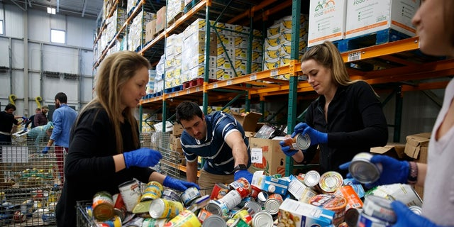 George Washington University School of Medicine students, Katie Coerdt, Paige Dekker, and Caitlin Merely sort canned food as they wear disposable gloves at Capital Area Food Bank in Washington on Thursday. The students are volunteering at the food bank because their medical rounds were cancelled because of the coronavirus outbreak.