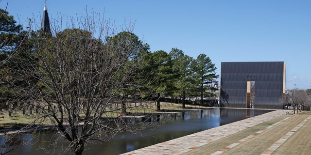 A visitor sits next to the reflecting pool at the Oklahoma City National Memorial and Museum in Oklahoma City, Okla., March 18, 2020. (Associated Press)