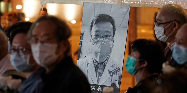 In this Feb. 7, 2020, file photo, people wearing masks attend a vigil for Chinese doctor Li Wenliang, who was reprimanded for warning about the outbreak of the new coronavirus, in Hong Kong.
