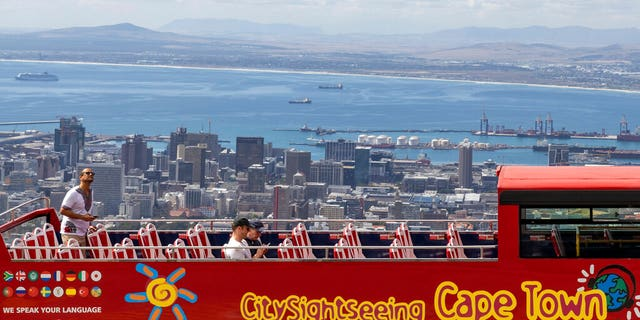 An open-air double decker sightseeing bus stops on the slopes of Table Mountain, overlooking Cape Town, South Africa Friday. (AP Photo)