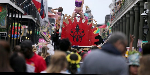 A woman dances atop a makeshift float on Bourbon Street on Mardi Gras day in New Orleans. (AP Photo/Rusty Costanza, File)