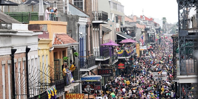 """Bourbon Street is a sea of humanity on Mardi Gras day in New Orleans. In the city here, the old saying """"Let the good times roll"""" has given way to a new municipal maxim: """"Wash your hands."""" A month ago the city was awash in people and steeped in its annual tradition of communal joy — the Mardi Gras season. (AP Photo/Rusty Costanza, File)"""