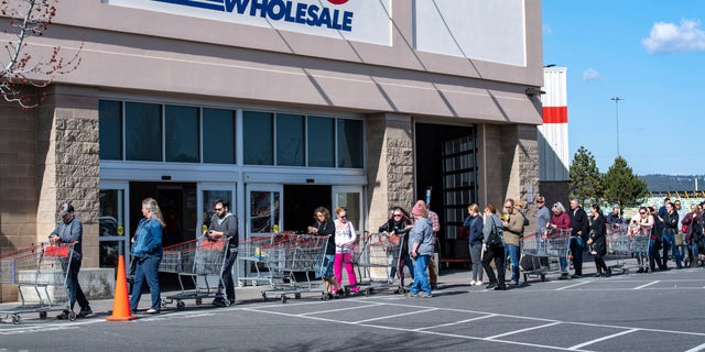 At the Costco in Spokane Valley, Wash., the store is practicing social distancing by limiting how many customers can be in the store at one time. A line wrapped around the building on March 20, but was moving so that the wait was only around 10 to 15 minutes. (Colin Mulvany/The Spokesman-Review via AP)