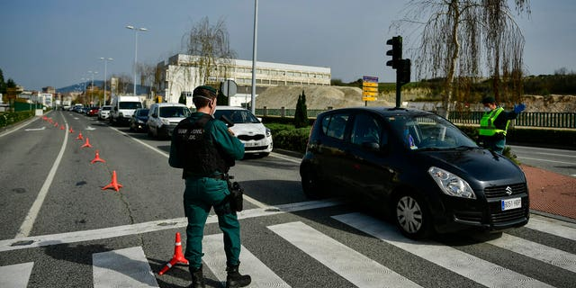 Spanish Civil Guard officers at a checkpoint to stop drivers from trying to leave the city, in Pamplona, northern Spain, Saturday, March 21, 2020. For many people the coronavirus causes mild or moderate symptoms, but for some it causes more severe illness, especially in older adults and people with existing health problems. (AP Photo/Alvaro Barrientos)