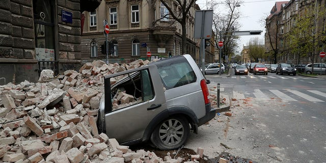 A car is crushed by falling debris after an earthquake in Zagreb, Croatia, Sunday, March 22, 2020. A strong earthquake shook Croatia and its capital on Sunday, causing widespread damage and panic. (Associated Press)