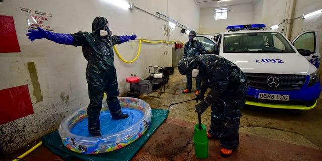 Volunteer workers of Search and Rescue (SAR) with special equipment, disinfect a volunteer while disinfecting police car at Local Police station to prevent the spread of coronavirus COVID-19, in Pamplona, northern Spain, Sunday, March 22, 2020. For some people the COVID-19 coronavirus causes mild or moderate symptoms, but for some it causes severe illness. (AP Photo/Alvaro Barrientos)