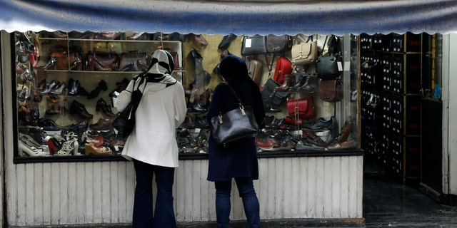 Two women look at shoes of a shop in a mostly empty street in a commercial district in downtown Tehran, Iran, Sunday, March 22, 2020. On Sunday, Iran imposed a two-week closure on major shopping malls and centers across the country to prevent spreading the new coronavirus. Pharmacies, supermarkets, groceries and bakeries will remain open. (AP Photo/Vahid Salemi)
