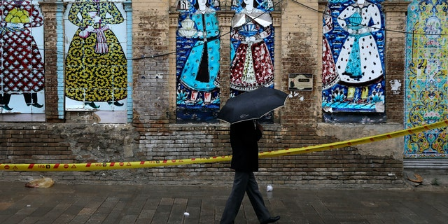 A man shelters from the rain with an umbrella as he walks past an old building decorated with a replica of Iranian old paintings in a mostly empty street in a commercial district in downtown Tehran, Iran, Sunday, March 22, 2020. On Sunday, Iran imposed a two-week closure on major shopping malls and centers across the country to prevent spreading the new coronavirus. Pharmacies, supermarkets, groceries and bakeries will remain open. (AP Photo/Vahid Salemi)