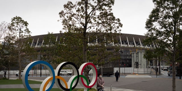 A woman pauses for photos next to the Olympic rings near the New National Stadium in Tokyo, Monday, March 23, 2020. The IOC will take up to four weeks to consider postponing the Tokyo Olympics amid mounting criticism of its handling of the coronavirus crisis that now includes a call for delay from the leader of track and field, the biggest sport at the games. (AP Photo/Jae C. Hong)