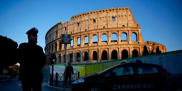 Italian carabinieri patrol Rome's Colosseum at dusk, Monday, March 23, 2020.