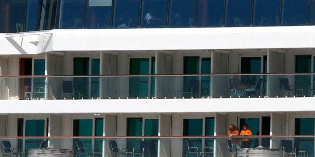 Two people look out from the Norwegian Jewel cruise ship in Honolulu on March 23. Passengers from the cruise ship that was turned away from other ports before arriving in Hawaii are being taken to Honolulu airport for chartered flights home. (AP Photo/Caleb Jones)