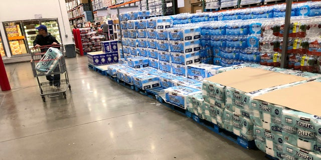 A shopper pushes a cart past a dwindling supply of toilet paper and hand towels in a Costco warehouse as shoppers continue to buy paper products in response to the spread of the coronavirus on March 23 in Lone Tree, Colo. (AP Photo/David Zalubowski)