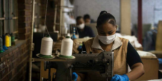 A woman sews high-quality face masks at a furniture factory in Eldorado Park, Johannesburg. (AP Photo/Shiraaz Mohamed)