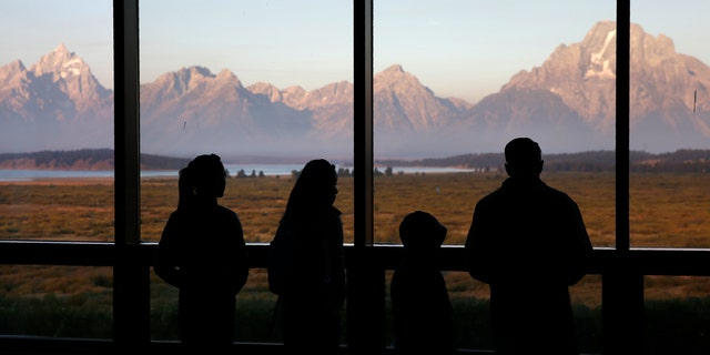 Visitors watch the morning sun illuminate the Grand Tetons from within the Great Room at the Jackson Lake Lodge in Grand Teton National Park north of Jackson, Wyo. in this file photo. (AP Photo/Brennan Linsley,File)