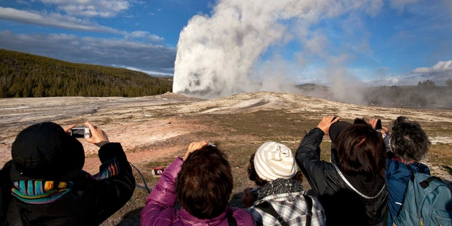 Tourists photograph Old Faithful erupting on schedule late in the afternoon in Yellowstone National Park, Wyo. (AP Photo/Julie Jacobson, File)
