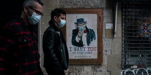 People walk past a poster that reads 'I want you to stay home', by artist TvBoy amid a lockdown in Barcelona, Spain, Tuesday, March 24, 2020.