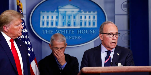 President Donald Trump and Dr. Anthony Fauci, the director of the National Institute of Allergy and Infectious Diseases, listening as White House chief economic adviser Larry Kudlow spoke about the coronavirus Tuesday at the White House. (AP Photo/Alex Brandon)