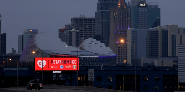 A sign urges residents to stay home as motorists drive past downtown Tuesday, March 24, 2020 on the first day of a stay-at-home order in Kansas City, Mo. Kansas City and surrounding counties instituted a 30-day mandatory stay-at-home order in an effort to stem the spread of the coronavirus. (AP Photo/Charlie Riedel)