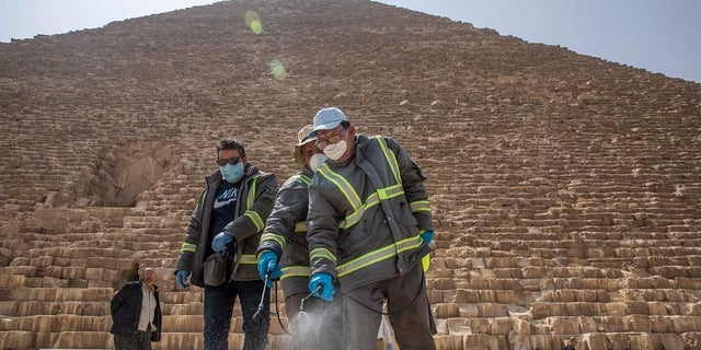 Municipal workers sanitize the walkways around the Giza pyramid complex on Wednesday in hopes of curbing the spread of the new coronavirus outbreak in Egypt. (AP Photo/Nariman El-Mofty)