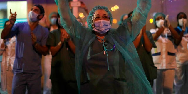 FILE: Health workers react as people applaud from their houses in support of the medical staff that are working on the COVID-19 virus outbreak at the Jimenez Diaz Foundation University hospital in Madrid, Spain.