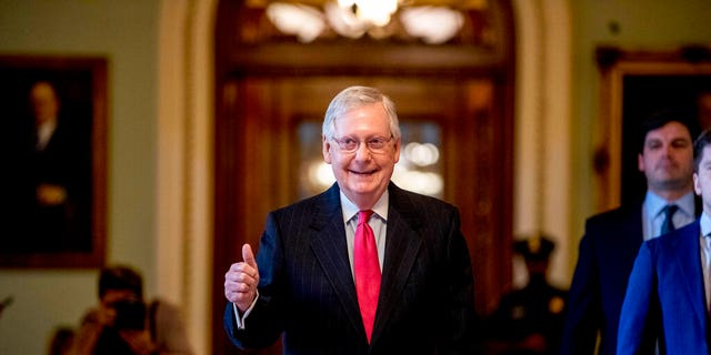 Senate Majority Leader Mitch McConnell of Ky. gives a thumbs up as he leaves the Senate chamber on Capitol Hill in Washington, Wednesday, March 25, 2020, where a deal has been reached on a coronavirus bill. (AP Photo/Andrew Harnik)