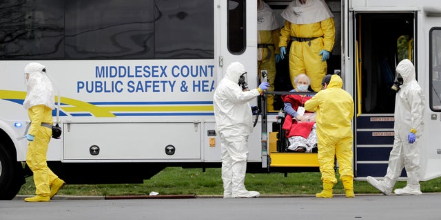 Residents from St. Joseph's Senior Home are helped onto buses in Woodbridge, N.J., Wednesday, March 25, 2020. More than 90 residents of the nursing home are being transferred to a facility in Whippany after 24 tested positive for COVID-19, according to a spokeswoman for CareOne.