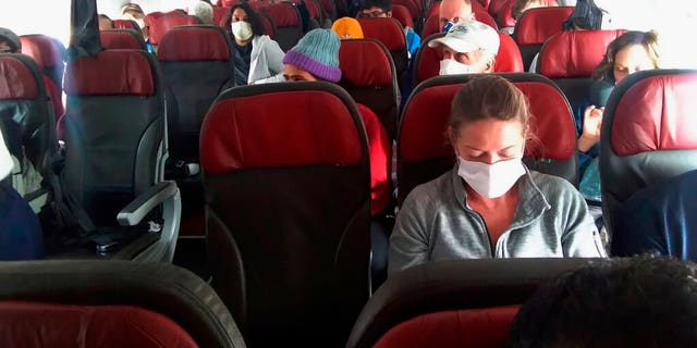 In this photo provided by a passenger who requested to be anonymous, passengers get ready before the doors close on a flight departing from Cusco, Peru, Wednesday, March 25, 2020. (Courtesy photo via AP)
