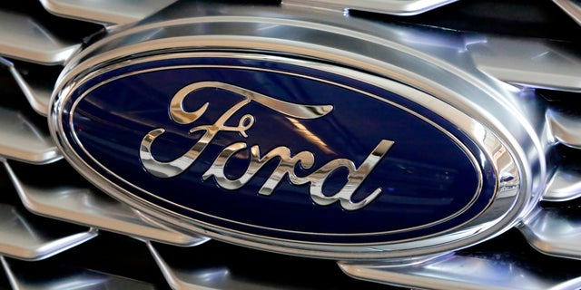 A Ford logo on the grill of a 2018 Ford Explorer on display at the Pittsburgh Auto Show in Feb. 2018. Ford Motor Company has announced plans to make 50,000 ventilators at one of its Michigan plants over the next 100 days in an effort to arm those on the front lines with equipment to fight COVID-19. (AP Photo/Gene J. Puskar, File)