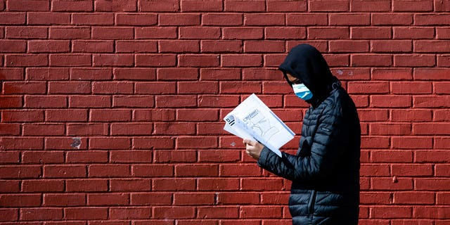 Terrell Bell, wearing a protective face mask, looks at a learning guide he picked up for his little sister at John H. Webster Elementary School in Philadelphia, Thursday, March 26, 2020. Gov. Tom Wolf's administration reported more new coronavirus-related deaths in Pennsylvania on Wednesday. Residents are ordered to stay home, with few exceptions. (AP Photo/Matt Rourke)