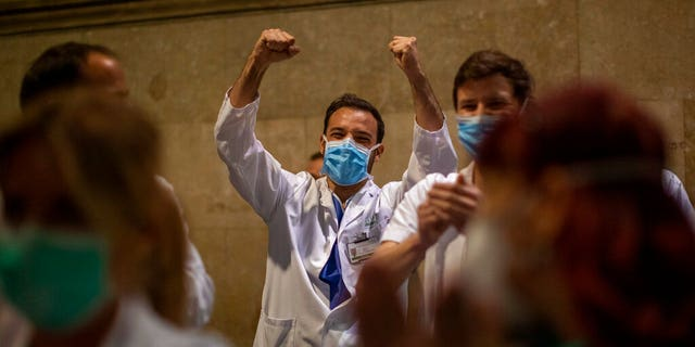 Health workers react as people applaud from their houses in support of the medical staff that are working on the COVID-19 virus outbreak at the main gate of the Hospital Clinic in Barcelona, Spain, Thursday, March 26, 2020.
