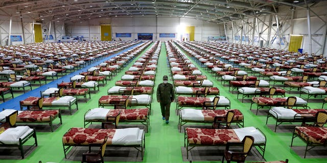 An Iranian army soldier walks past rows of beds at a temporary 2,000-bed hospital for COVID-19 coronavirus patients set up by the army at the international exhibition center in northern Tehran, Iran, on Thursday, March 26, 2020.