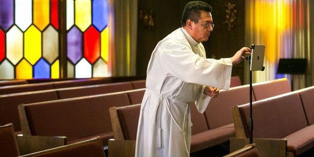 The Rev. César Vega sets up a tablet to livestream Mass to home-bound congregants Friday, March 27, 2020, at Holy Family Catholic Church in Yakima, Wash. (Amanda Ray/Yakima Herald-Republic via AP)