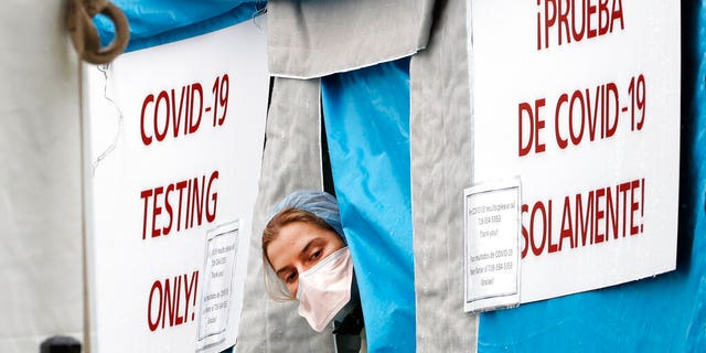 A medical worker sticks her head outside a COVID-19 testing tent set up outside Elmhurst Hospital Center in New York, Saturday, March 28, 2020. The hospital is caring for a high number of coronavirus patients in the city, and New York leads the nation in the number of cases, according to Johns Hopkins University, which is keeping a running tally. (AP Photo/Kathy Willens)