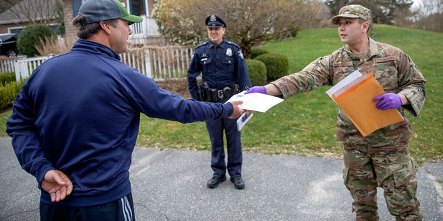 Rhode Island Air National Guard TSgt. William Randall, right, handing out an information sheet to a man self-quarantining at his home in Westerly, R.I.