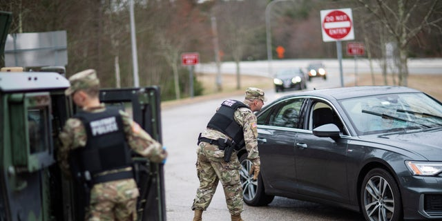 A member of the Rhode Island National Guard Military Police directs a motorist with New York license plates at a checkpoint on Interstate 95 in Hope Valley, R.I., March 28, 2020, (Associated Press)