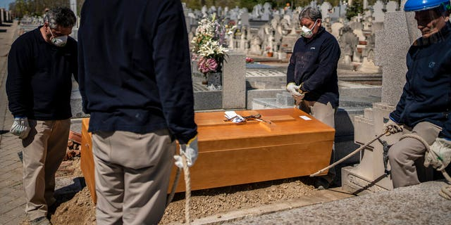 Undertakers take a moment while a priest and family, not seen, pray during the burial of an elderly victim of the COVID-19 at the Almudena cemetery in Madrid, Spain, Saturday March 28, 2020. In Spain, where stay-at-home restrictions have been in place for nearly two weeks, the official number of deaths is increasing daily. The new coronavirus causes mild or moderate symptoms for most people, but for some, especially older adults and people with existing health problems, it can cause more severe illness or death. (AP Photo/Olmo Calvo)